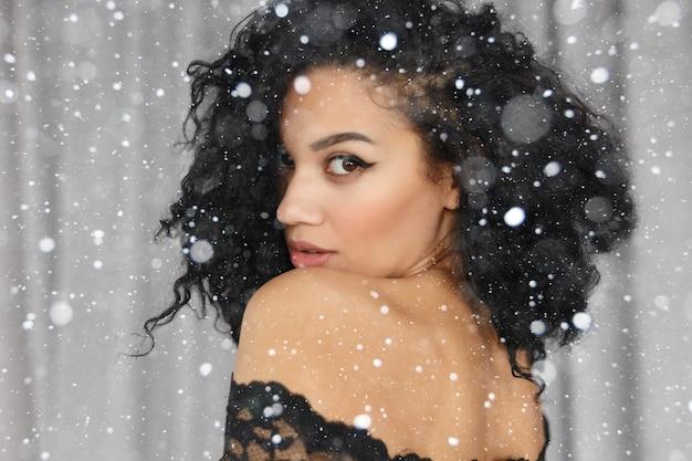 Sneeuw, winter, kerstmis, mensen, schoonheidsconcept - gelukkige serene jonge vrouw met mooie olijfkleurige huid en krullende haar ideale huid en bruine ogen. close-up portret over sneeuw achtergrond