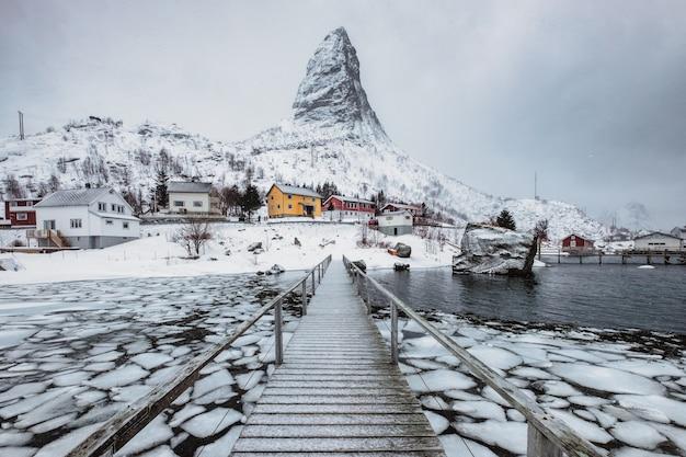 Sneeuwberg met skandinavisch dorp op kustlijn met houten brug bij lofoten-eilanden