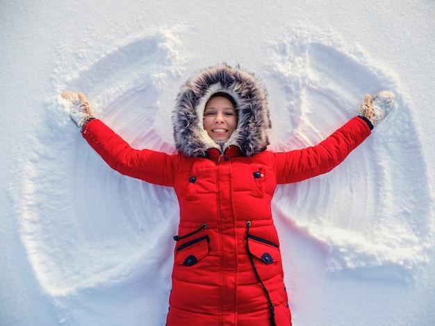 Sneeuwengel gemaakt door een gelukkige vrouw in de sneeuw. bovenste vlakke bovenaanzicht.