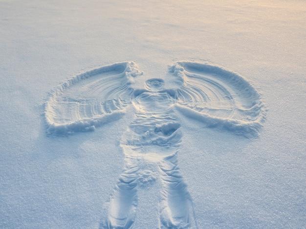 Sneeuwengel gemaakt in de witte sneeuw in de avond. bovenste vlakke bovenaanzicht.