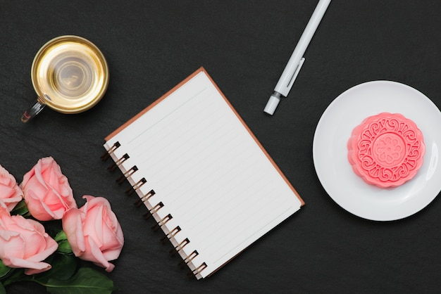 Sneeuwhuid mooncake en kopje thee met bloemen. notitieblok openen met kopie-ruimte.