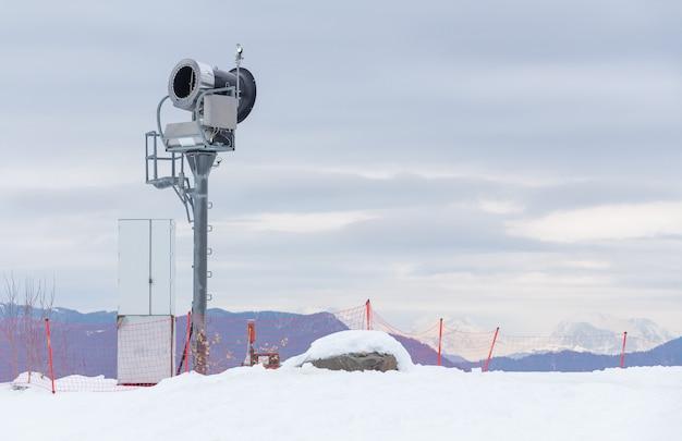 Sneeuwkanon in de bergen. het landschap van het skigebied.