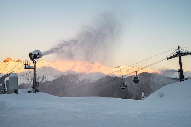Sneeuwkanon van avondbergen en kabelwagen. voorbereiding op het skiseizoen
