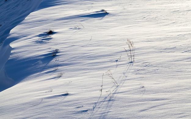 Sneeuwlaag na de zware sneeuwval op het oppervlak zijn er hobbels en schaduwen op de rand van de heuvel, het gras groeit sneeuw, zonnige winterochtend