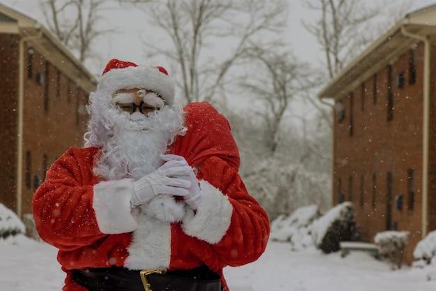 Sneeuwlandschap kerstman draagt een zware tas, loopt langs de straat tijdens een sneeuwval