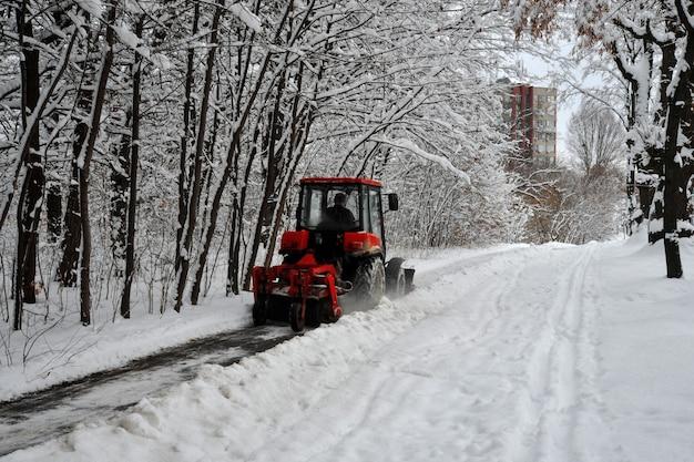 Sneeuwmachine, rode tractor reinigt de sneeuw van de sneeuw