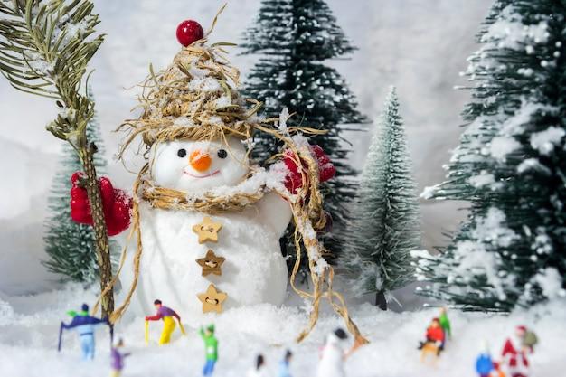 Sneeuwman en mensen in dennenbossen tijdens de winter