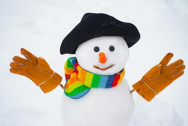 Sneeuwman in een hoed met handschoenen en sjaal buiten