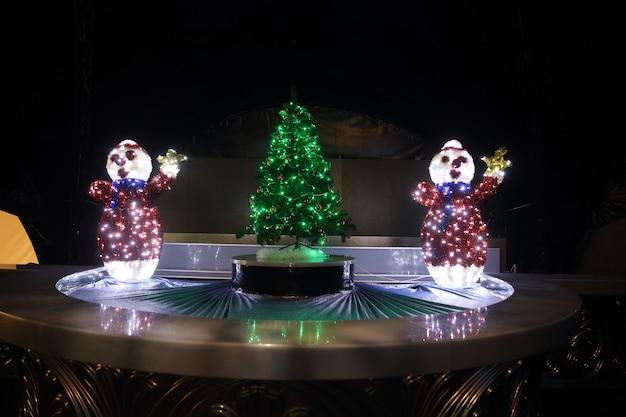 Sneeuwmannen en kerstboom in de straat van de stad op kerstnacht. vakantie concept