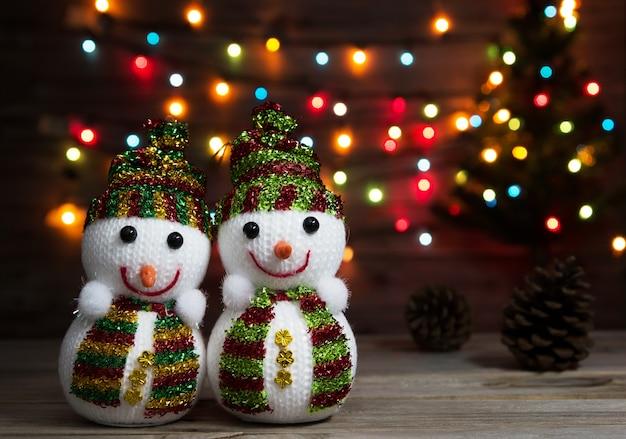 Sneeuwmanpoppen op kerstmislicht en kerstmisboomachtergrond.