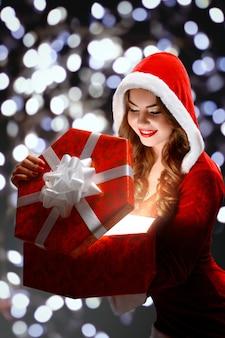 Sneeuwmeisje in rood kostuum die houdend een gift, openingsdoos glimlachen.