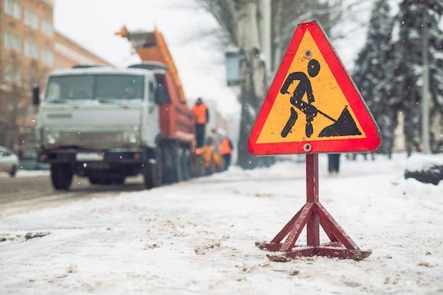 Sneeuwploeg verwijdert sneeuw uit de straat van de stad. waarschuwing verkeersbord. werkblazer sneeuwblazer werk. reinigen besneeuwde bevroren wegen.