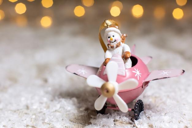 Sneeuwpop in een roze vliegtuig met een propeller feestelijk decor, warme bokehlichten.