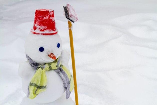 Sneeuwpop in rode muts en sjaal gemaakt door kinderen. close-up, selectieve aandacht