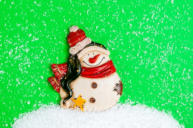 Sneeuwpopbeeldje op een groene muur. een sneeuwjacht gemaakt van kunstmatige sneeuw.