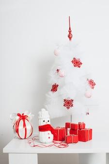 Sneeuwpoppendecoratie bij de kerstboom met rode geschenkdoos