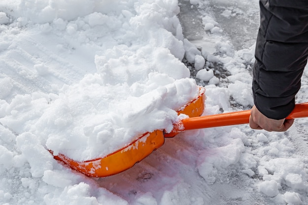 Sneeuwruimen met een schop van dichtbij