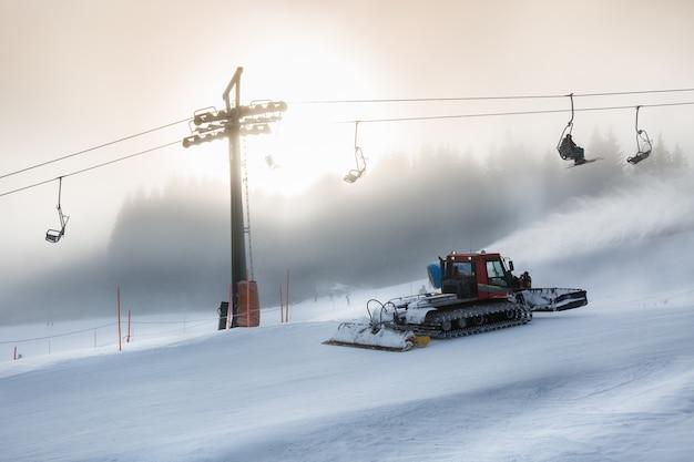Sneeuwruimmachine bezig met hoge skihelling bij sneeuwstorm