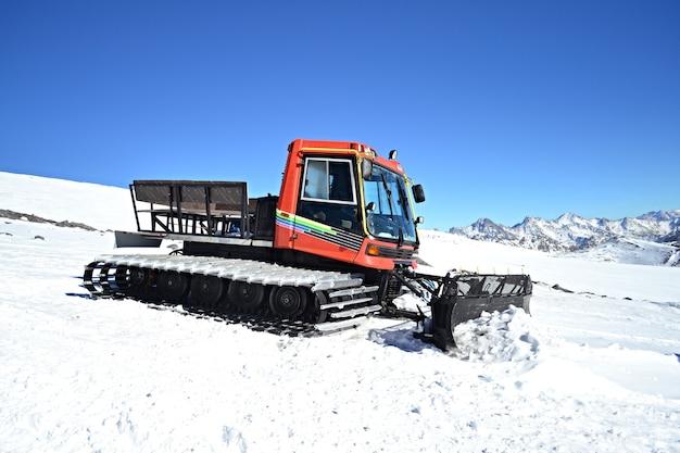 Sneeuwschuiver in de bergen reinigt de weg van sneeuw