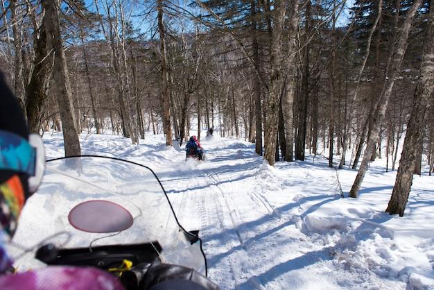 Sneeuwscooter in blizzard door het bos en het bos, openluchtsportconcept.