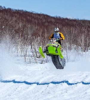 Sneeuwscooter in hoogspringen boven spoor.