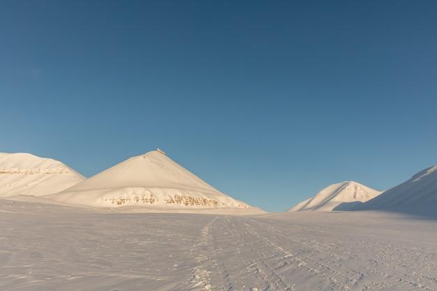 Sneeuwscootersporen in noordpool de winterlandschap met sneeuw behandelde bergen op svalbard, noorwegen