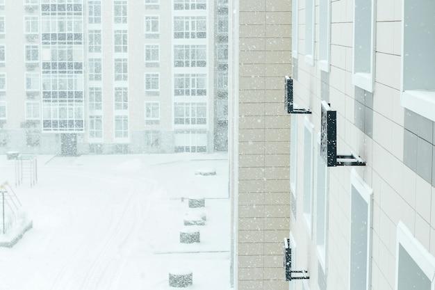 Sneeuwstorm in de stad. de tuin van een woongebouw is bedekt met sneeuw