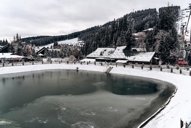 Sneeuwt winterlandschap met het bevroren meer in de bergen. bevroren oppervlak van het water. winterseizoen concept