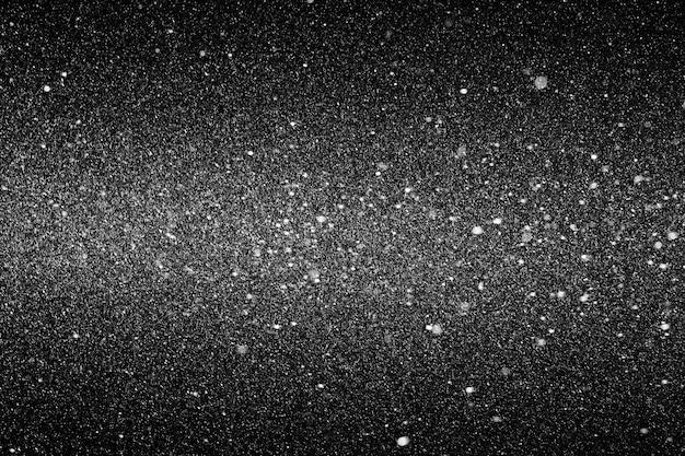 Sneeuwtextuur in de lucht op een zwarte achtergrond. selectieve aandacht.