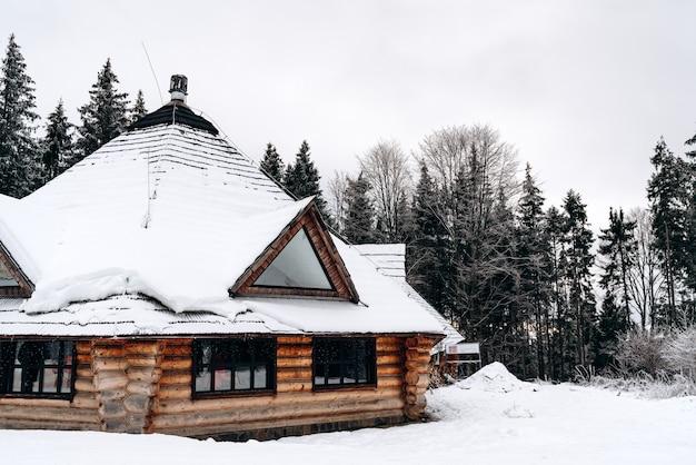 Sneeuwval in het dorp. oud blokhuis in de sneeuw. traditioneel typisch huis of villa op het platteland in de winter. houten huisje onder sneeuwvlokken
