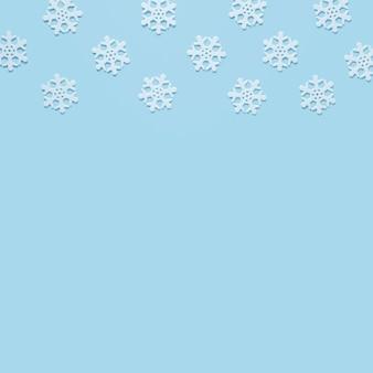 Sneeuwvlok op baby blauwe achtergrond met exemplaarruimte