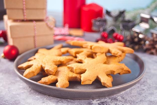 Sneeuwvlok vormige zelfgemaakte kerstkoekjes op de plaat met kerstversiering op de achtergrond.