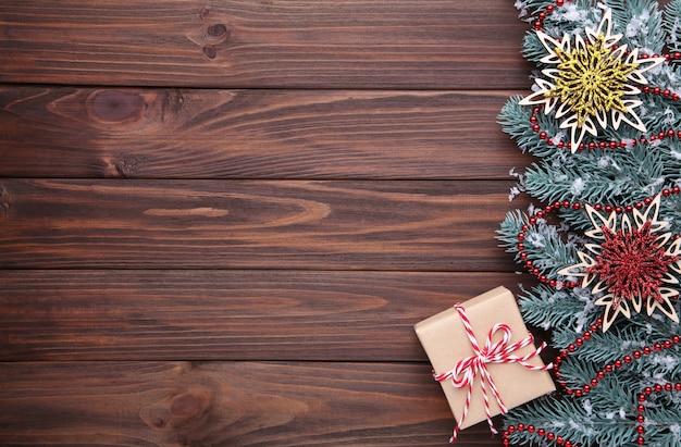 Sneeuwvlokken en cadeau op een bruine houten achtergrond.