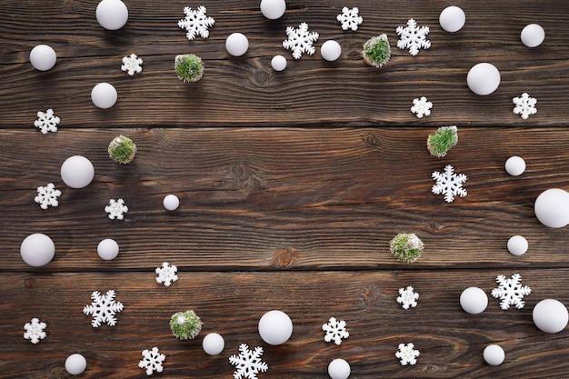 Sneeuwvlokken en sneeuwballenkader op houten achtergrond.