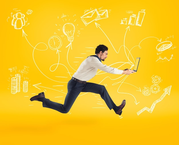 Snel bedrijfsconcept met zakenman die met laptop loopt. gele achtergrond