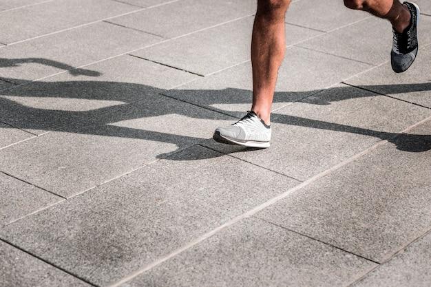 Snel en woedend. benen van een sterke afro-amerikaanse man tijdens het hardlopen