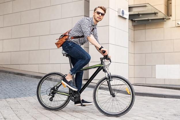 Snel voertuig. slimme knappe man met een fiets in de stad terwijl hij op kantoor gaat werken