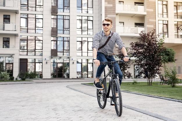 Snelle fiets. positieve gelukkige man die lacht terwijl hij geniet van zijn rit op de fiets