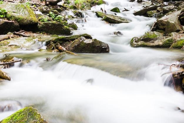 Snelle kleine bergrivier die onder stenen stroomt
