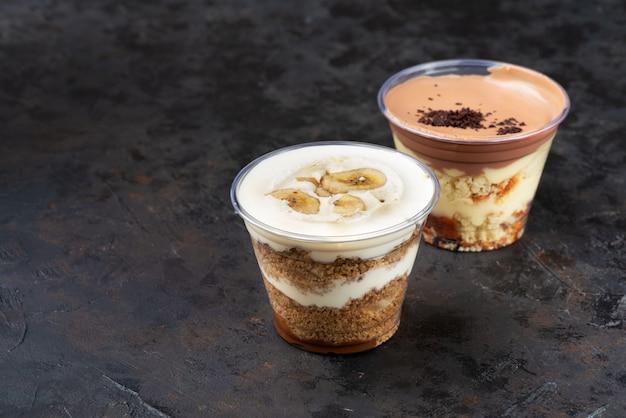 Snelle levering van eten. banoffee pie dessert in beker met verse banaan op houten achtergrond, selectieve aandacht, kopie ruimte, afhaaldoos