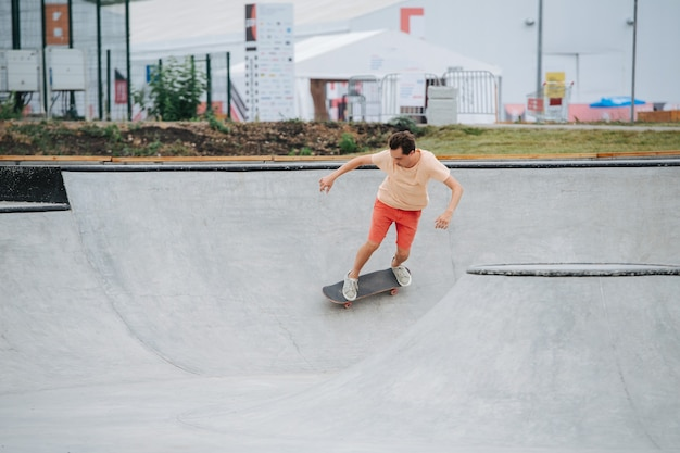 Snelle man skater in kleurrijke kleding rijden op haar bord op quarter pipe cirkel in skatepark. wilde gok.