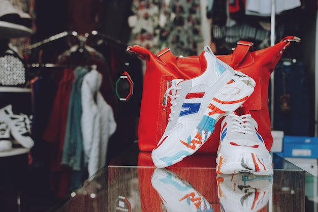 Snelle mode concept. rode handtas en schoenen op plank in winkel, winkel.