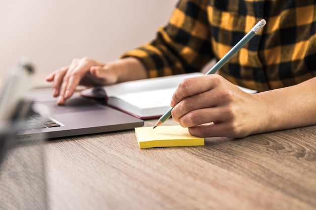 Snelle notitie. close-up handen van een zakenvrouw, student of freelancer in geel shirt het maken van een notitie op notitie