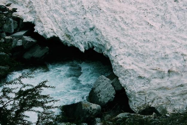 Snelle rivier stroomt onder een rotsformatie in de buurt van rotsen en planten