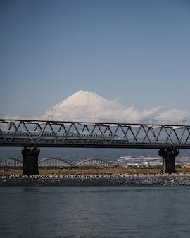 Snelle shinkansen-trein over de fuji-rivier met een betoverende fuji-berg