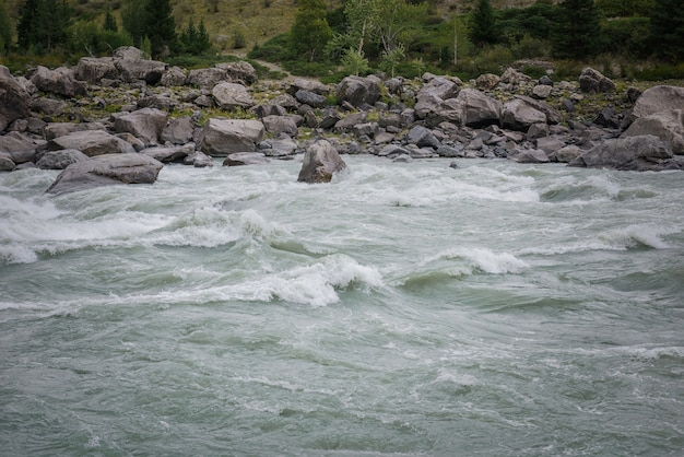 Snelle stroming van water in bergrivier op de achtergrond van rotsachtige oevers, gebied om te raften, hoge moeilijkheidsgraad.