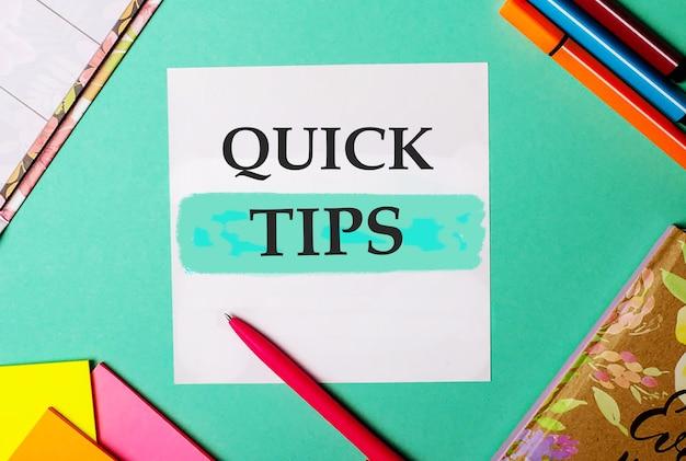 Snelle tips geschreven op een turkooizen achtergrond in de buurt van heldere stickers, blocnotes en stiften