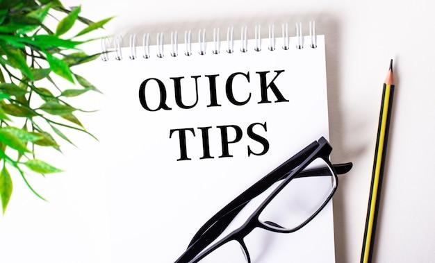 Snelle tips is geschreven in een wit notitieboekje naast een potlood, een bril met een zwart montuur en een groene plant.