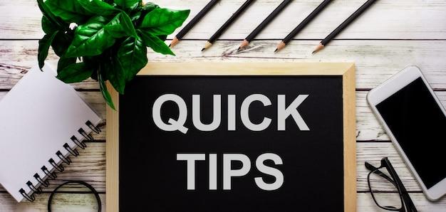 Snelle tips is in het wit geschreven op een zwart bord naast een telefoon, notitieblok, bril, potloden en een groene plant.