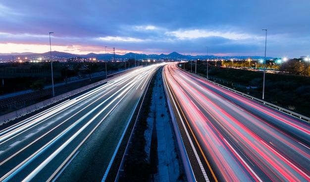 Snelweg bij zonsondergang, voertuigen rijden in twee richtingen lichtsporen verlaten